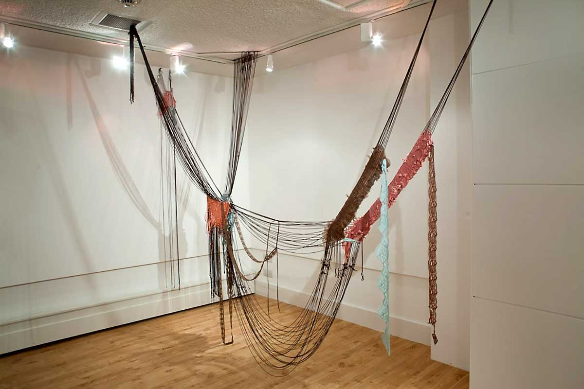 SINCE I FELL FOR YOU | 2009/10. Installed at Rochester Art Gallery for Thread bare Exhibition Woven anti-form sculpture. vintage and second hand clothing including Marks & Spencer's nightwear and petticoats, and Laura Ashley Velvet Dress. Rayon upholstery cord. Steel tacks. Dimensions : H 250cm x D 120cm x L 340cm variable. Photo : David Ramkalawon