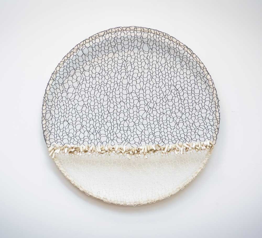ON THE SHORE - 2017   Wall work in paper wire and porcelain on wooden frame   Technique: Knitting, modelling, embroidery   Size: diameter 60 cm x depth 9 cm
